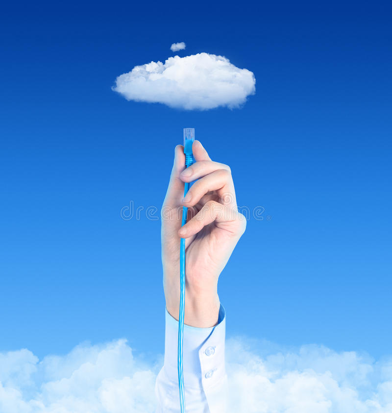 Connecting To Cloud Concept. Hand with the cable connected to the cloud. Conceptual image on cloud computing theme