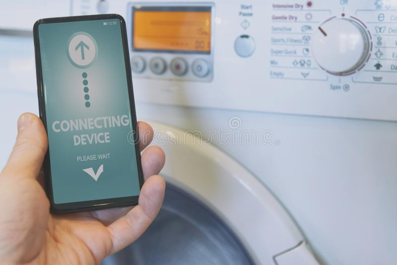 Connecting washing machine with smart phone stock photography