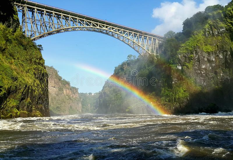 The connection between Zimbabwe and Zambia. Bridge between Zimbabwe and Zambia with a rainbow below stock images