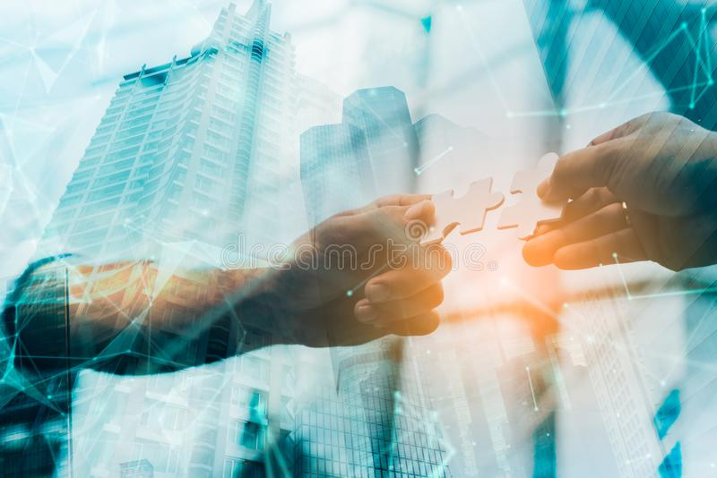 Connection concept. hands with pieces of jigsaw puzzle on Double royalty free stock images