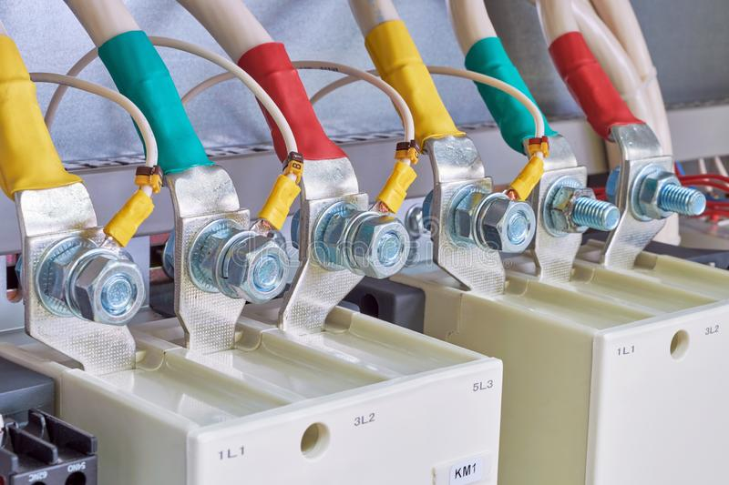 Connection of electrical cables and wires to industrial magnetic starters. Cables are marked with color. Bolted connection with nut. Modern production of stock image