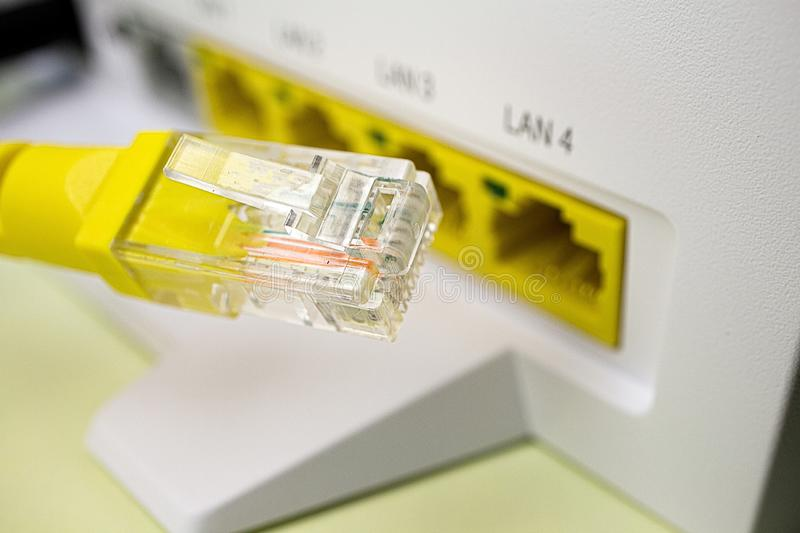 The connection to the local network via the home router, patch cord yellow closeup on the background. Of the router stock image