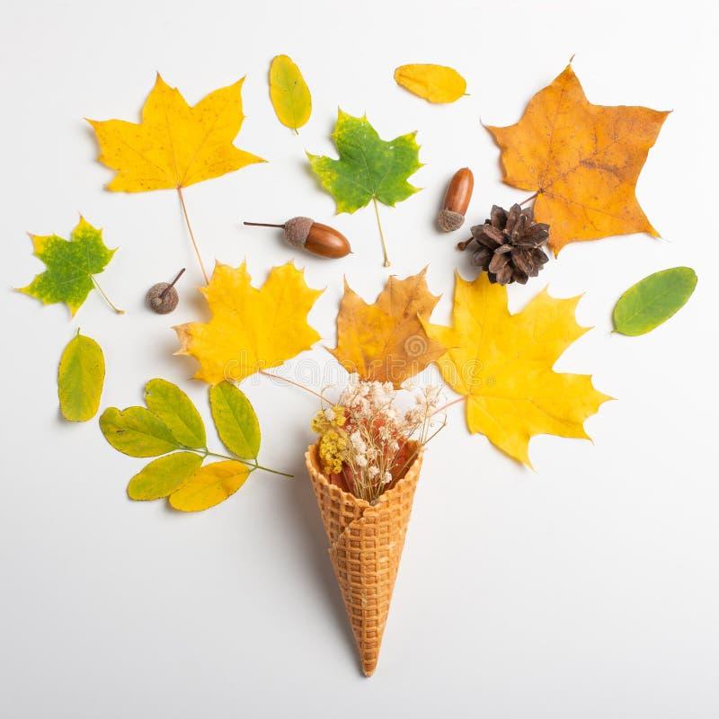 cono amarillo de la galleta con las hojas secadas de las hojas de otoño en un fondo blanco, ocioso plano, visión superior Arte fotos de archivo libres de regalías