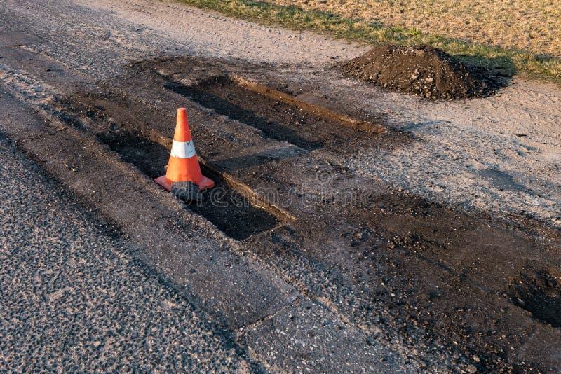 Cono anaranjado blanco del peligro del tráfico en la reparación de la carretera de asfalto imagen de archivo libre de regalías