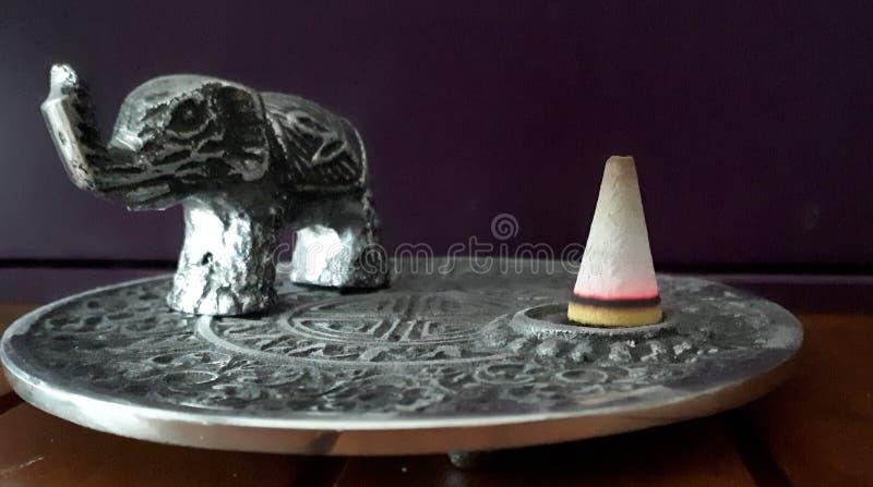 Cono ardiendo del incienso al lado de una figura del elefante fotos de archivo libres de regalías