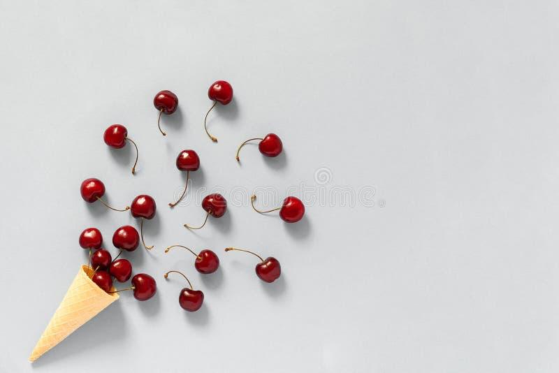 Cono de helado curruscante de la galleta con las cerezas dulces maduras rojas dispersadas Todavía vida en fondo gris copie el esp foto de archivo