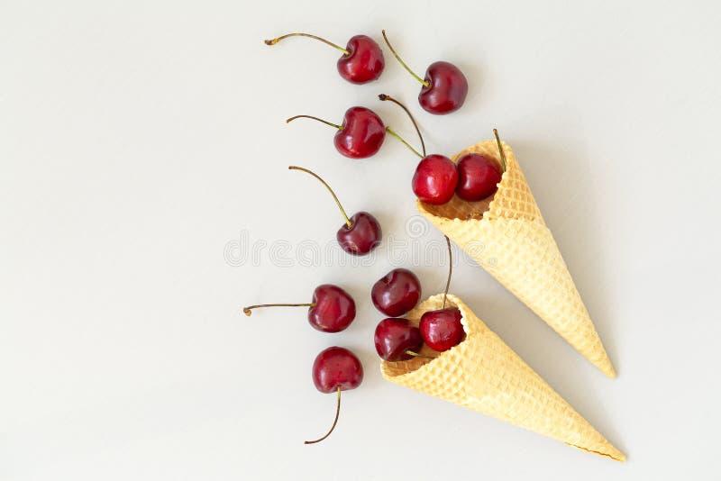 Cono de helado llenado de las cerezas en un fondo ligero gris Cereza fresca en un cono de la galleta Concepto del verano imagen de archivo