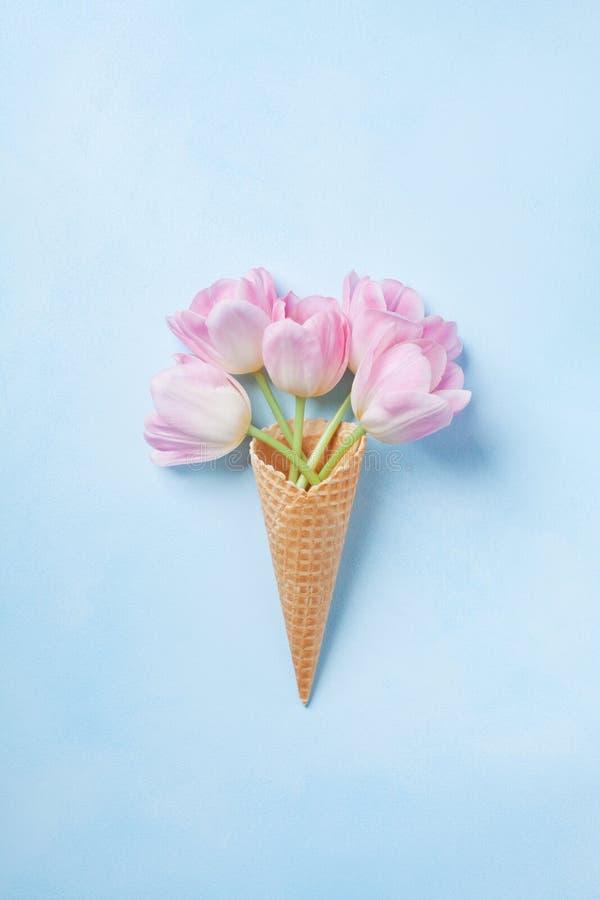 Cono de la galleta con el ramo rosado de los tulipanes en la opinión superior del fondo azul en colores pastel Endecha plana foto de archivo libre de regalías