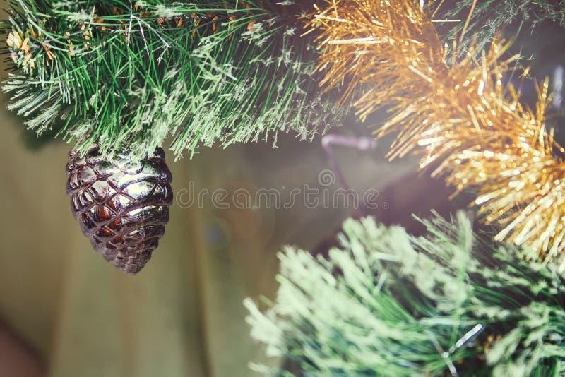 Cono de plata que cuelga en una rama de un árbol de navidad artificial adornado con una guirnalda del oro fotografía de archivo