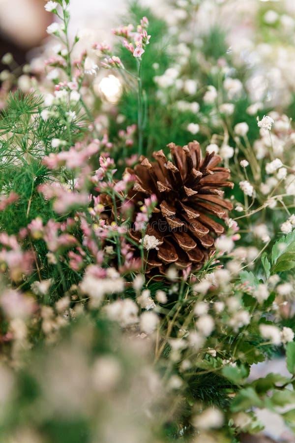 Cono decorato con i fiori e l'erba verde fotografia stock