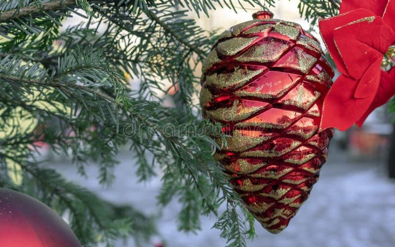 Cono del cedro rojo del juguete de la Navidad y flor de la poinsetia imagen de archivo