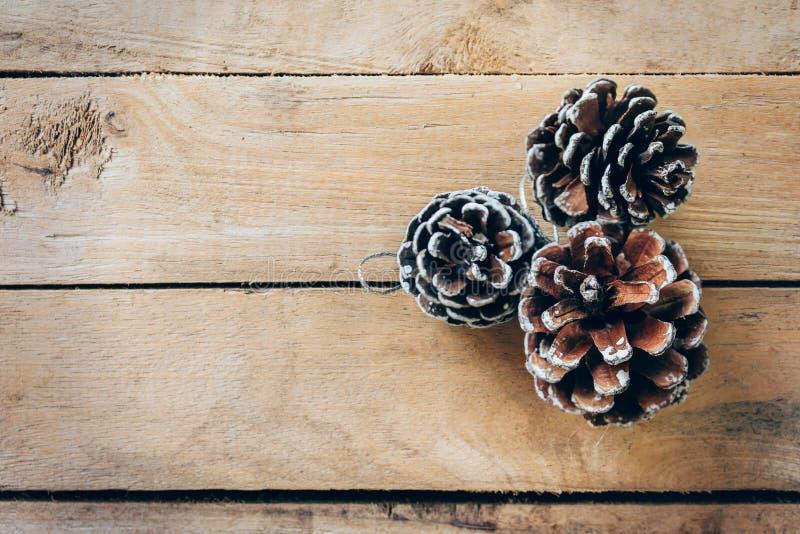 Cono del pino en el fondo de madera de la tabla con el espacio fotografía de archivo