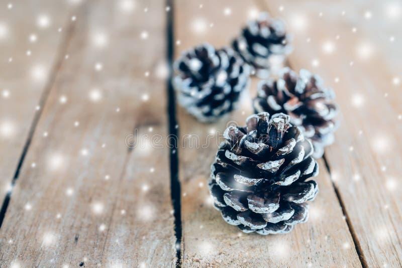 Cono del pino y nieve blanca en el fondo de madera de la tabla con el espacio foto de archivo