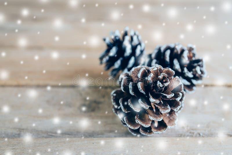 Cono del pino y nieve blanca en el fondo de madera de la tabla con el espacio imagenes de archivo