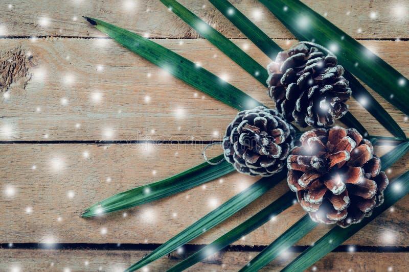 Cono del pino y nieve blanca en el fondo de madera de la tabla con el espacio fotos de archivo