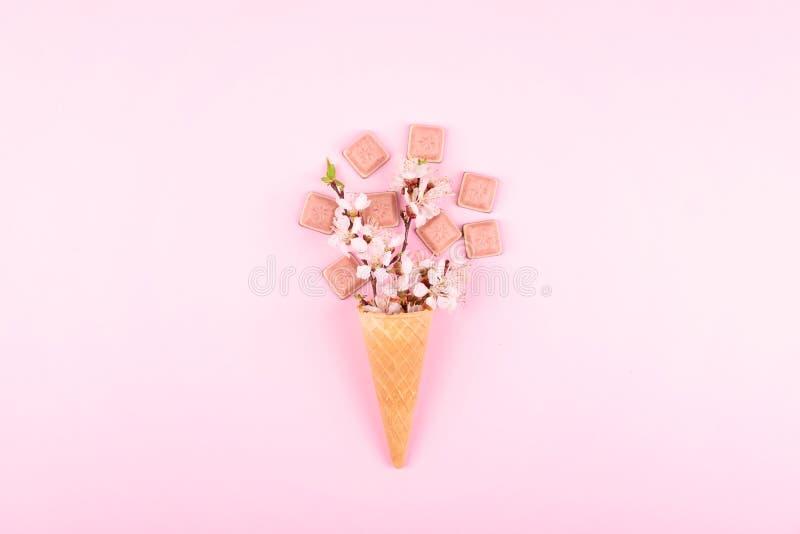 Cono della cialda del gelato con i fiori variopinti ed il cioccolato rosa su fondo rosa Disposizione piana Concetto minimo di com fotografie stock libere da diritti
