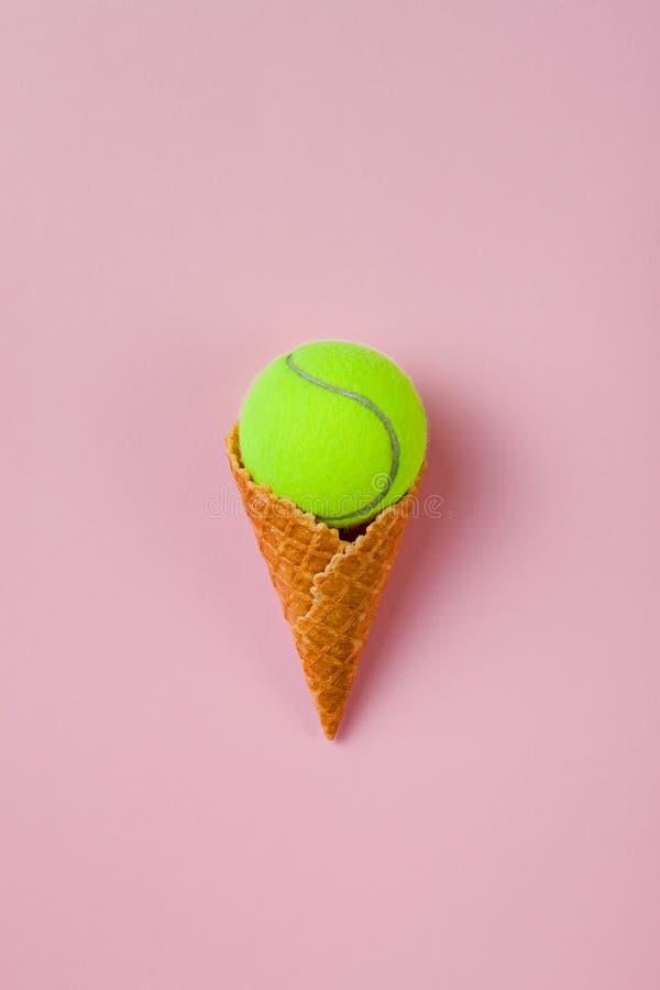 Cono gelato con pallina da tennis sul fondo di rosa pastello Disposizione piana immagini stock