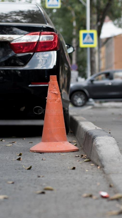 Cono viejo anaranjado del tráfico en el camino cerca de un cuidado fotos de archivo libres de regalías