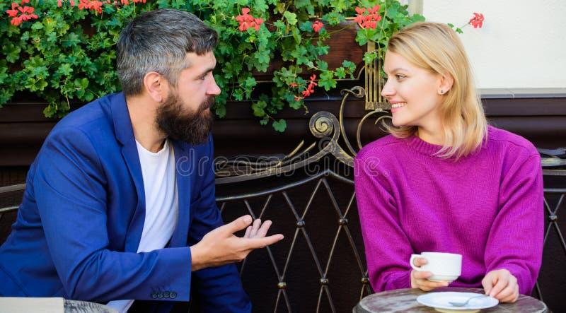 Conocidos convertidos reunión Hacer frente a la primera fecha de la gente Junte el café de consumición de la terraza Público casu fotografía de archivo libre de regalías
