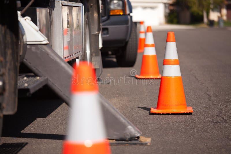 Conos anaranjados del peligro y carro utilitario en calle imagen de archivo libre de regalías