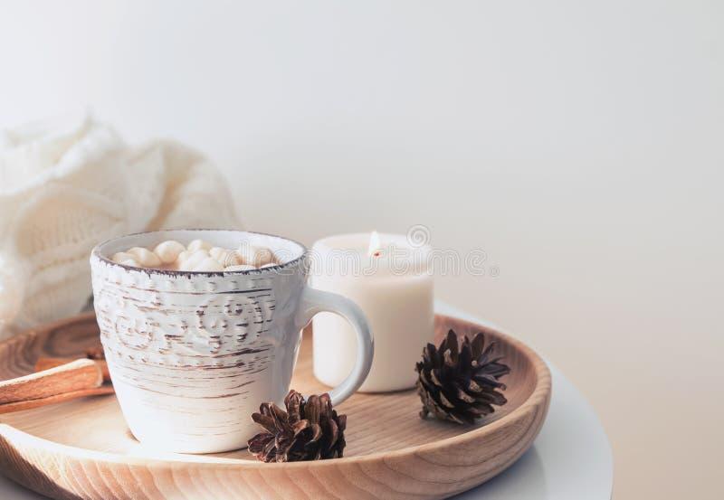 Conos calientes del cacao, de la vela y del pino en la bandeja de madera fotografía de archivo