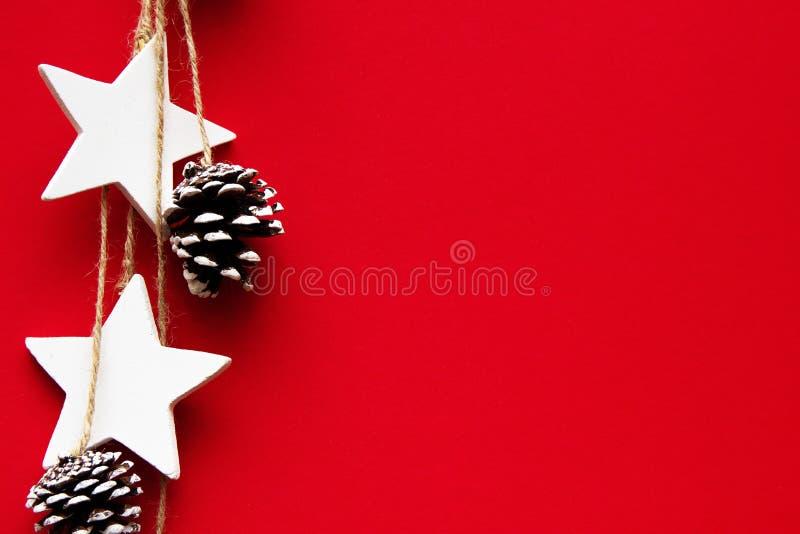 Conos del árbol de navidad, y estrellas en un fondo rojo fotos de archivo libres de regalías