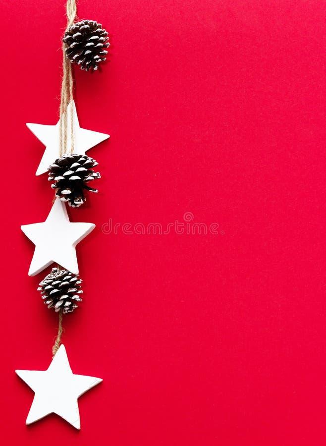 Conos del árbol de navidad, y estrellas en un fondo rojo imagenes de archivo