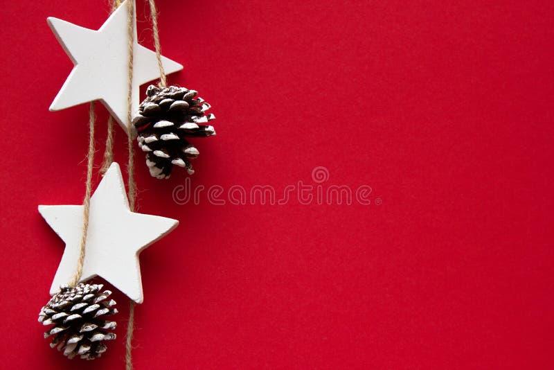 Conos del árbol de navidad, y estrellas en un fondo rojo fotografía de archivo libre de regalías