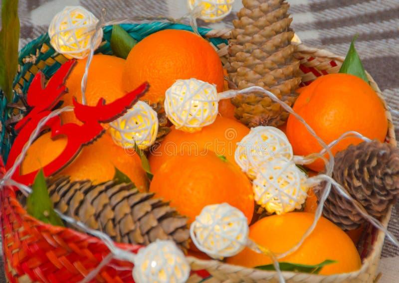Conos, naranjas y guirnalda en una cesta de la Navidad imagen de archivo libre de regalías