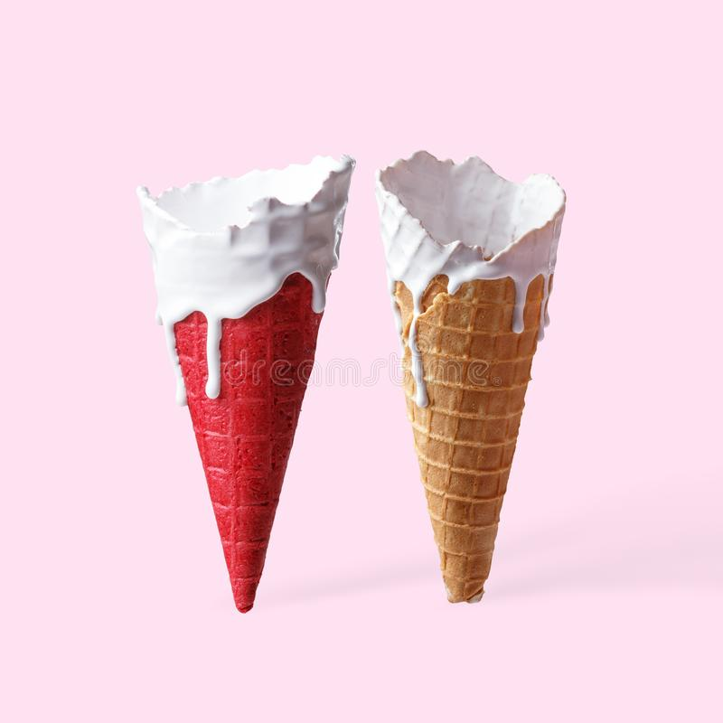 Conos para el helado en las manchas de la pintura blanca en un fondo rosa claro foto de archivo