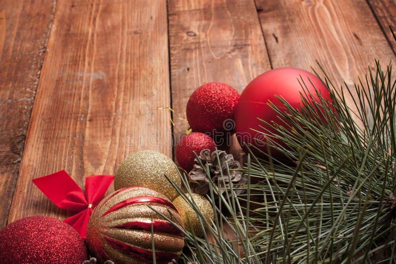 Conos rojos de las bolas, del pino y del ciprés de la Navidad con las ramitas en la madera t imágenes de archivo libres de regalías