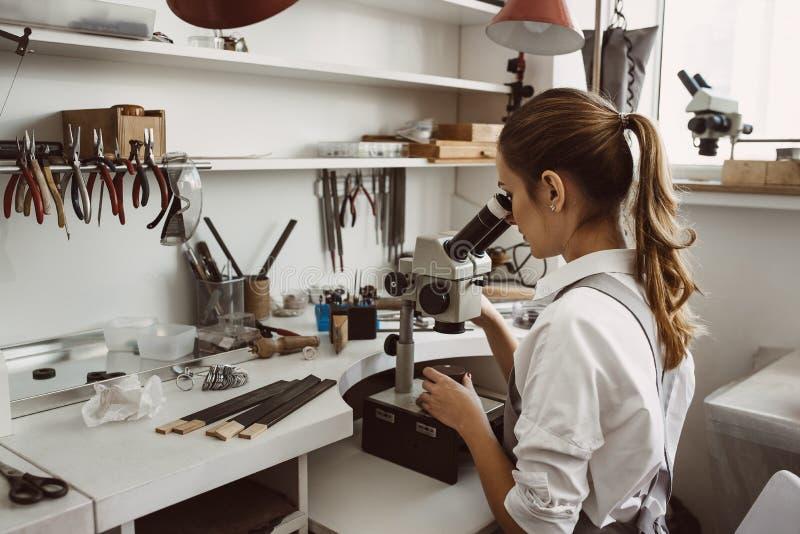 Conosce che cosa sta facendo Ritratto del gioielliere femminile che esamina il nuovo prodotto dei gioielli tramite il microscopio fotografie stock