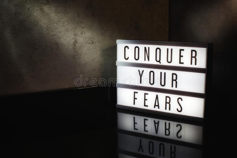 Conquer your fears motivational message. On a light box in a cinematic moody background royalty free stock photos