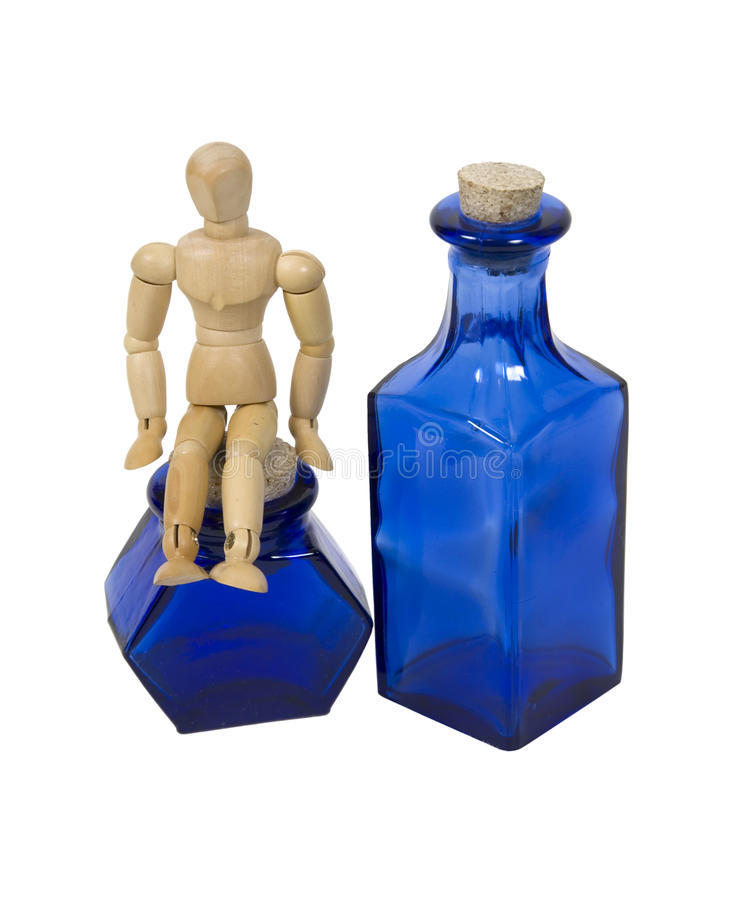 Conquering the blues. Shown by a model sitting on bright cobalt blue bottles lined up in a row - path included royalty free stock photography