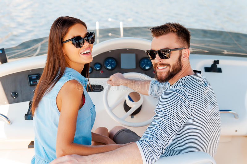 Conquering new marine ways together. Cheerful young couple looking at camera and smiling while driving yacht stock photos