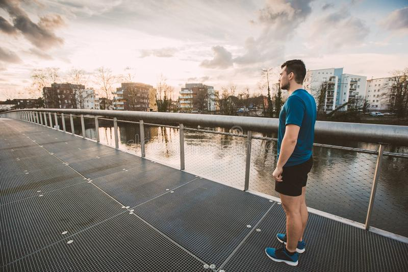 Conquering obstacles. Young athletic man prepare for a run practicing sport outdoors. Self overcome concept, conquering obstacles and win. Healthy lifestyle royalty free stock photography