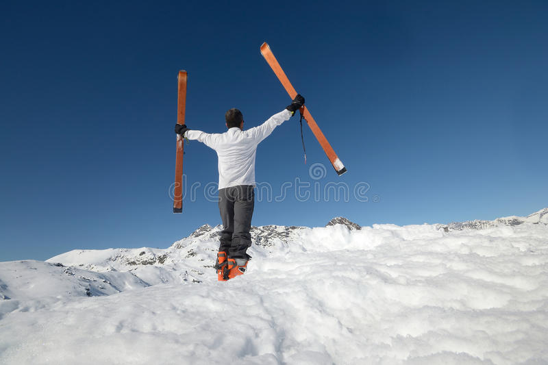 Conquering the summit. Alpinist conquering the summit by ski touring royalty free stock image