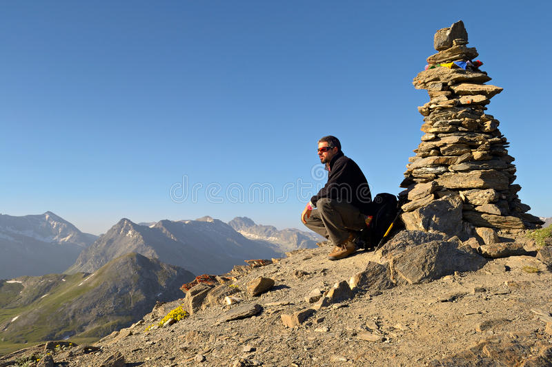 Conquering the summit. Alpinist conquering the summit by ski touring stock photo