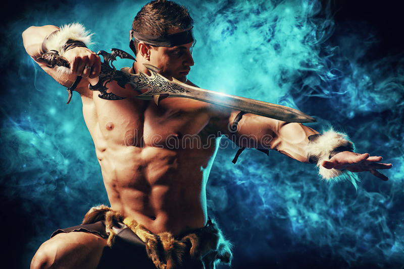 Conqueror. Portrait of a handsome muscular ancient warrior with a sword royalty free stock photography