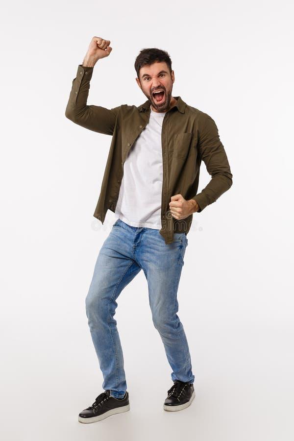 Conquista, sucesso e conceito de prêmio Estúdio vertical de comprimento integral alvejado e alegre macho com barba em casual imagem de stock