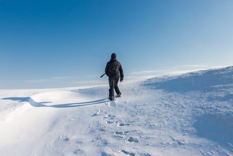 Conquistador de picos, subiendo una montaña nevosa imagen de archivo
