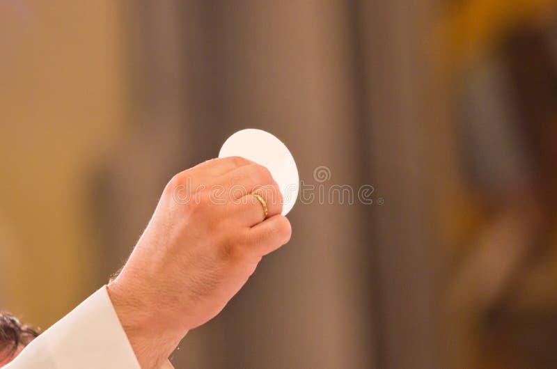 Consécration du corps du Christ dans les mains du wh de prêtre photo libre de droits