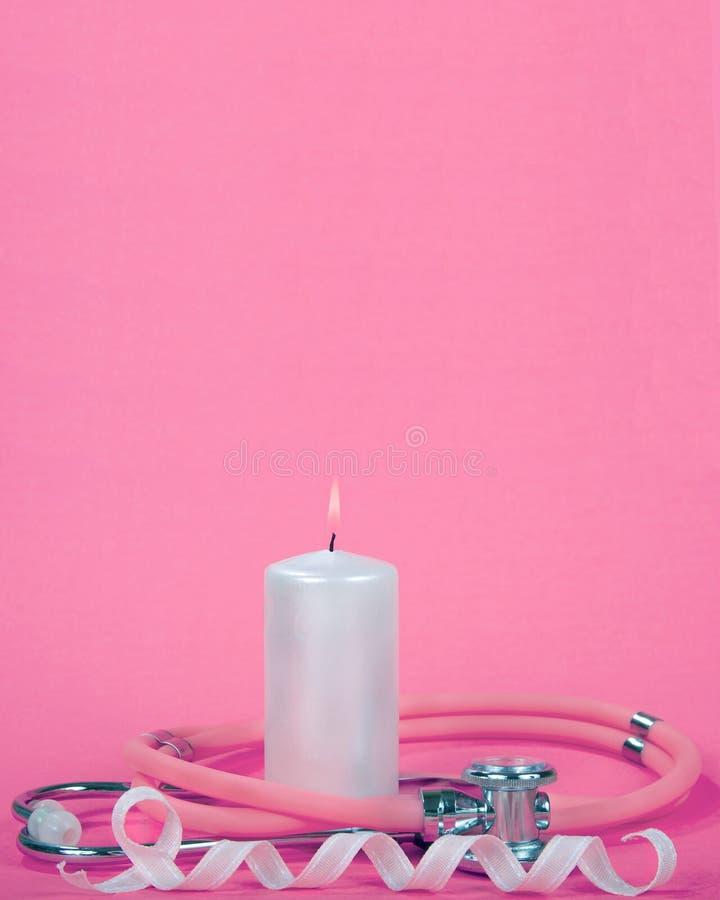Conscience de cancer du sein, bougie rose-clair brûlante avec le stéthoscope images libres de droits