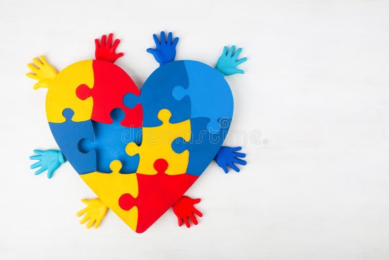 Conscientização do autismo do apoio das mãos do coração do enigma fotografia de stock