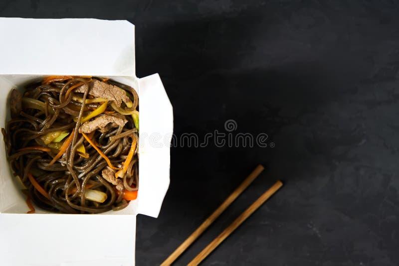 Consegna dei pranzi caldi in scatole Tagliatelle di Soba con manzo e le verdure su un fondo nero immagine stock