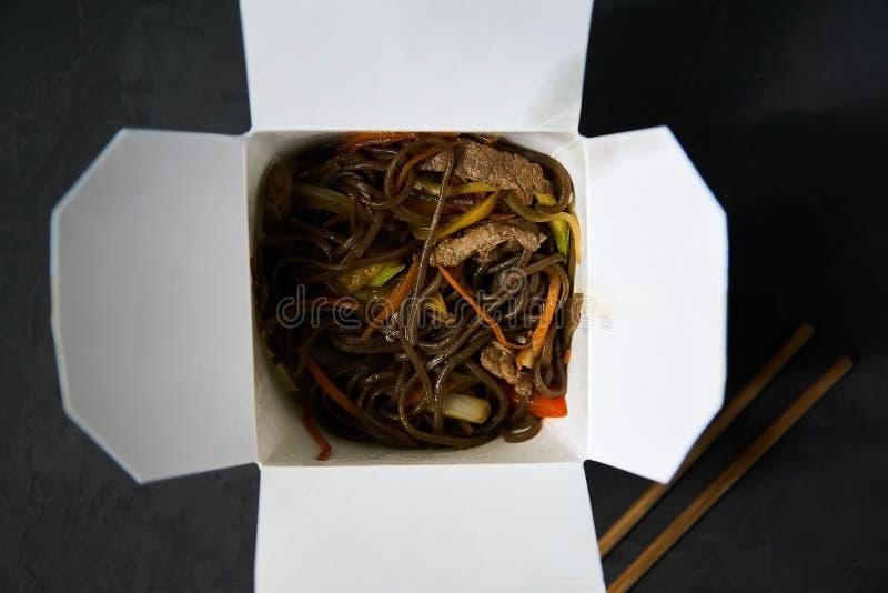 Consegna dei pranzi caldi in scatole Tagliatelle di Soba con manzo e le verdure su un fondo nero immagini stock libere da diritti