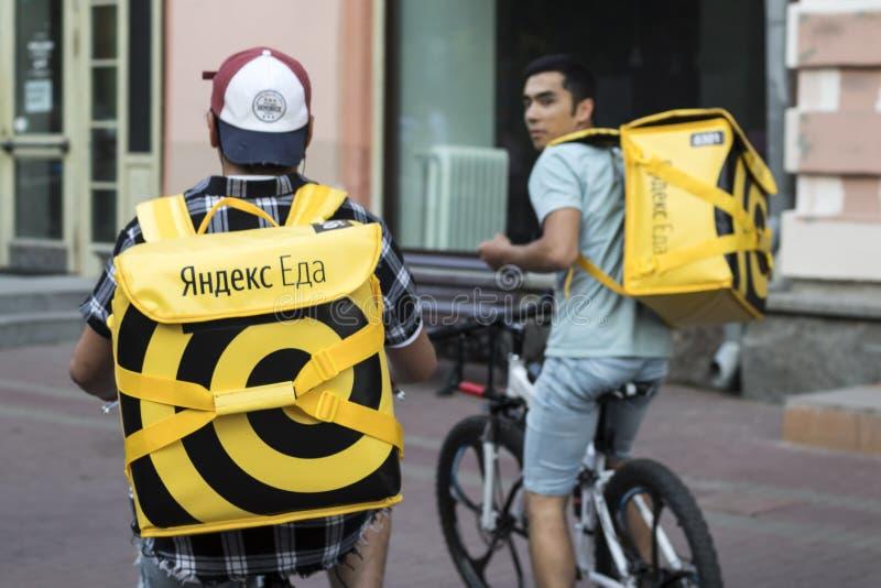 Consegna dell'alimento a Mosca - corriere in un cappello con i earflaps ed in un rivestimento giallo con l'alimento di Yandex del fotografia stock libera da diritti