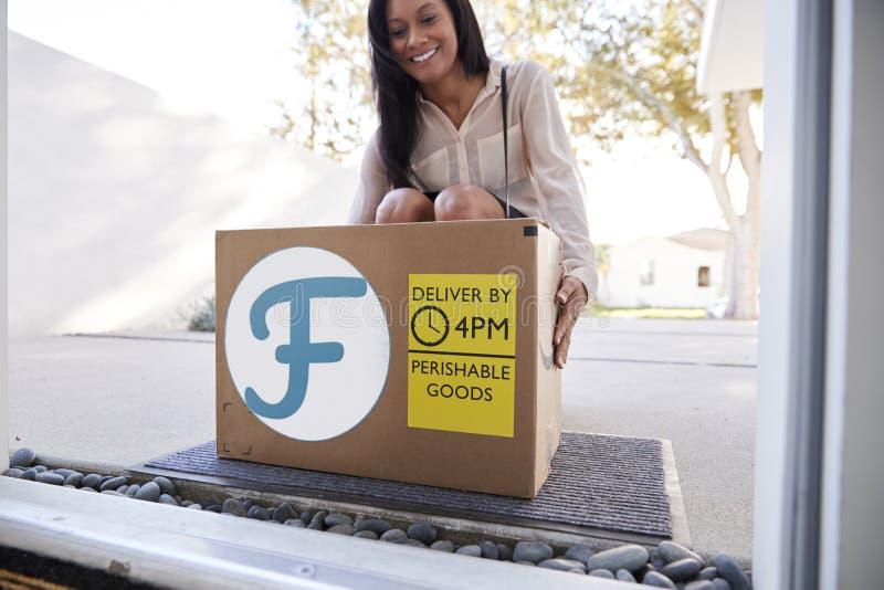 Consegna a domicilio dell'alimento fresco di Coming Home To della donna di affari in scatola di cartone fuori di Front Door fotografie stock libere da diritti