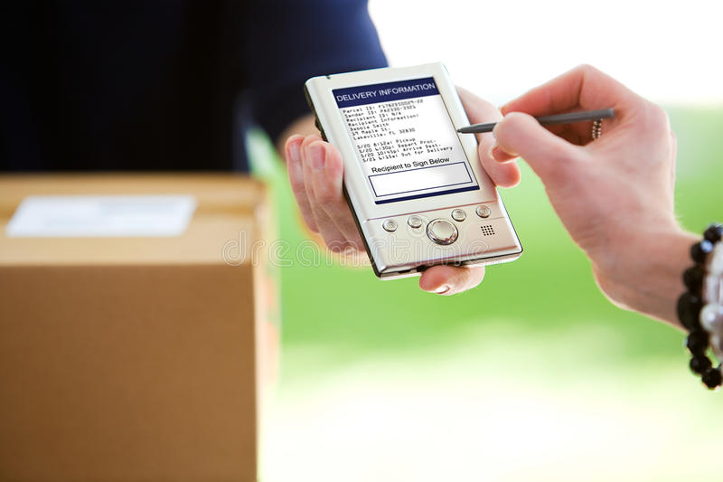 Consegna: Donna che firma il dispositivo di Digital immagini stock libere da diritti