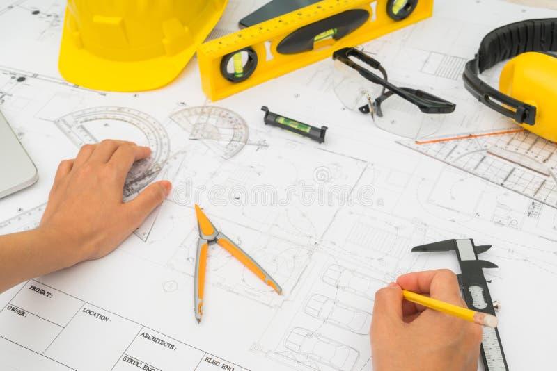 Consegni i piani della costruzione con lo strumento giallo di disegno e del casco fotografia stock